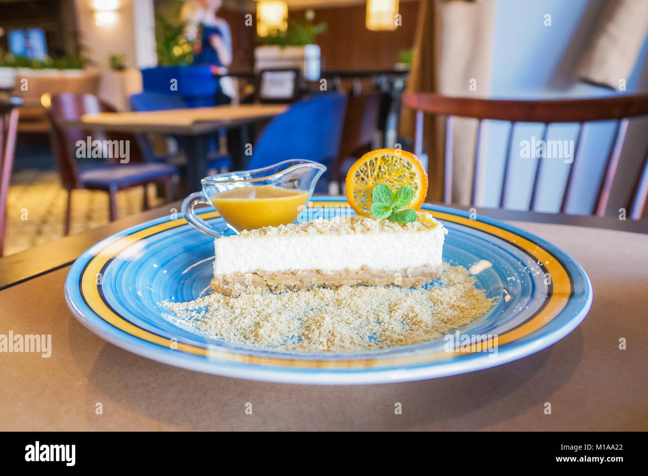Cheesecake with sea-buckthorn sauce in a blue with yellow stripe plate in a restaraunt - Stock Image