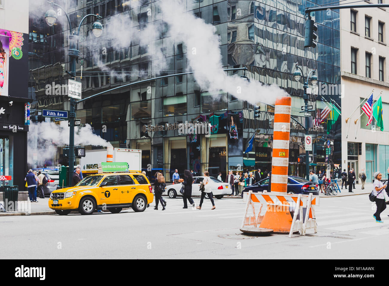 NEW YORK, NY - June 9th, 2014: steam vent cones in the streets of Manhattan among the traffic - Stock Image