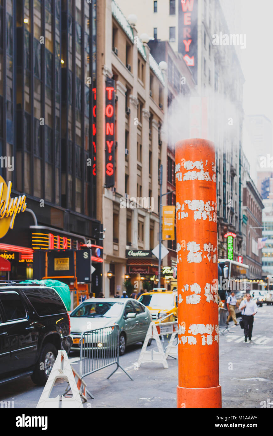 NEW YORK, NY - June 10th, 2014: steam vent cones in the streets of Manhattan among the traffic - Stock Image