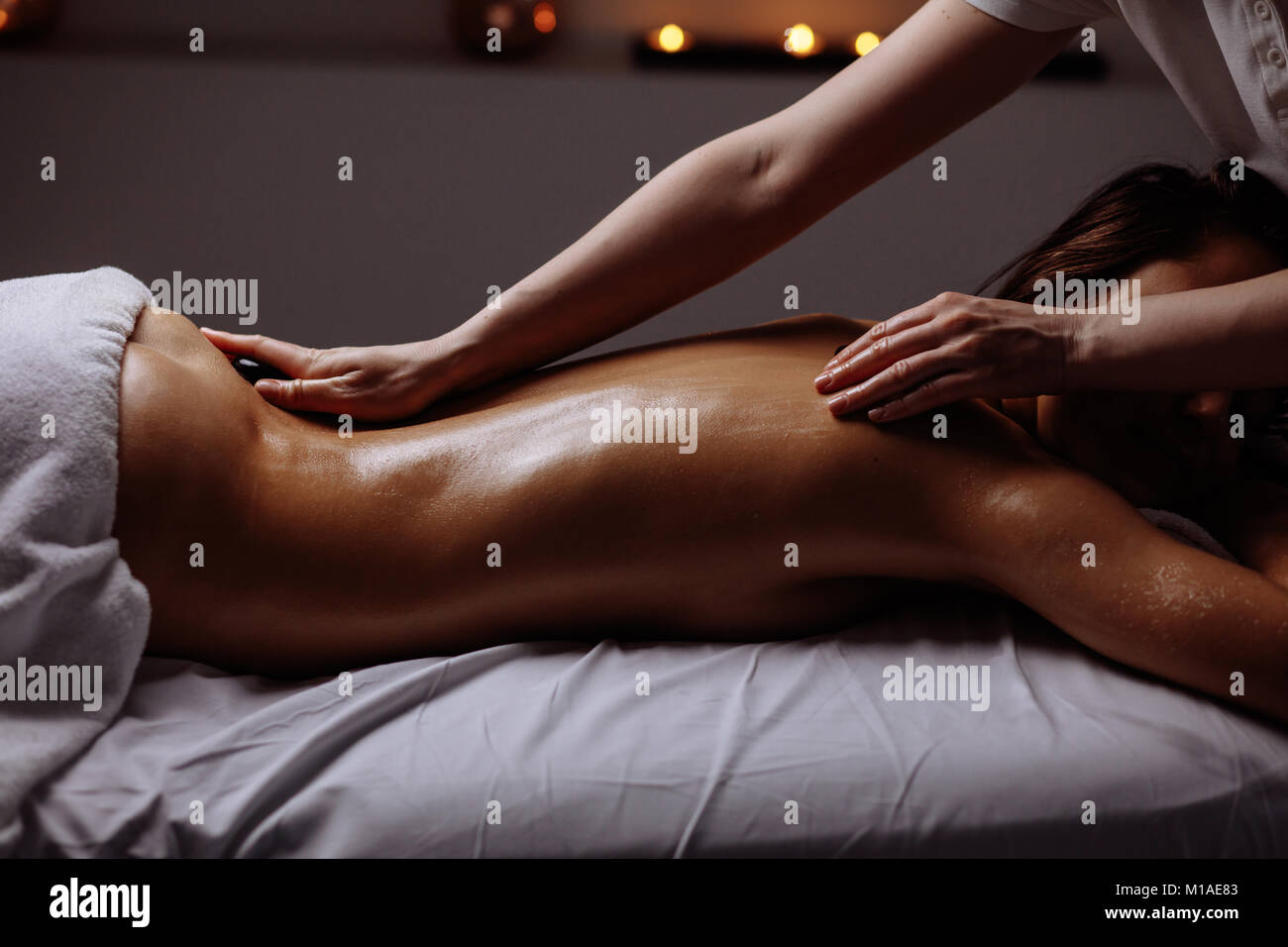 young Woman getting hot stone massage at spa salon - Stock Image