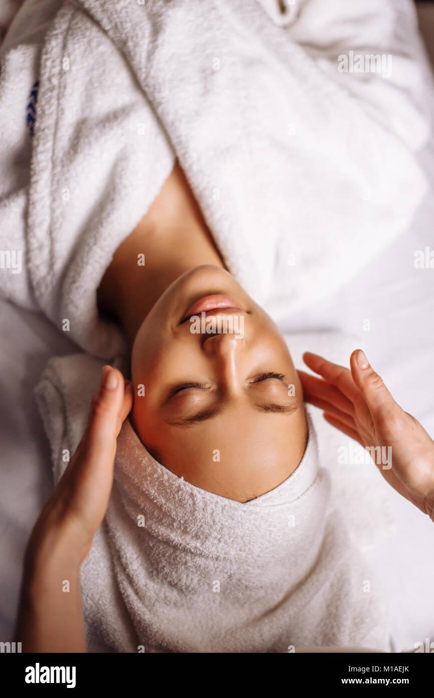 girl having spa facial massage in luxurious beauty salon - Stock Image