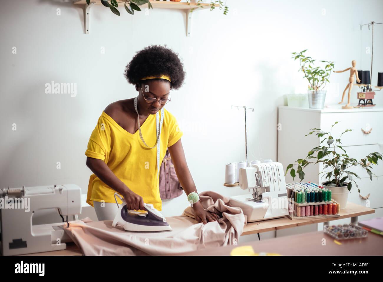 african Woman seamstress Ironing cloth - Stock Image