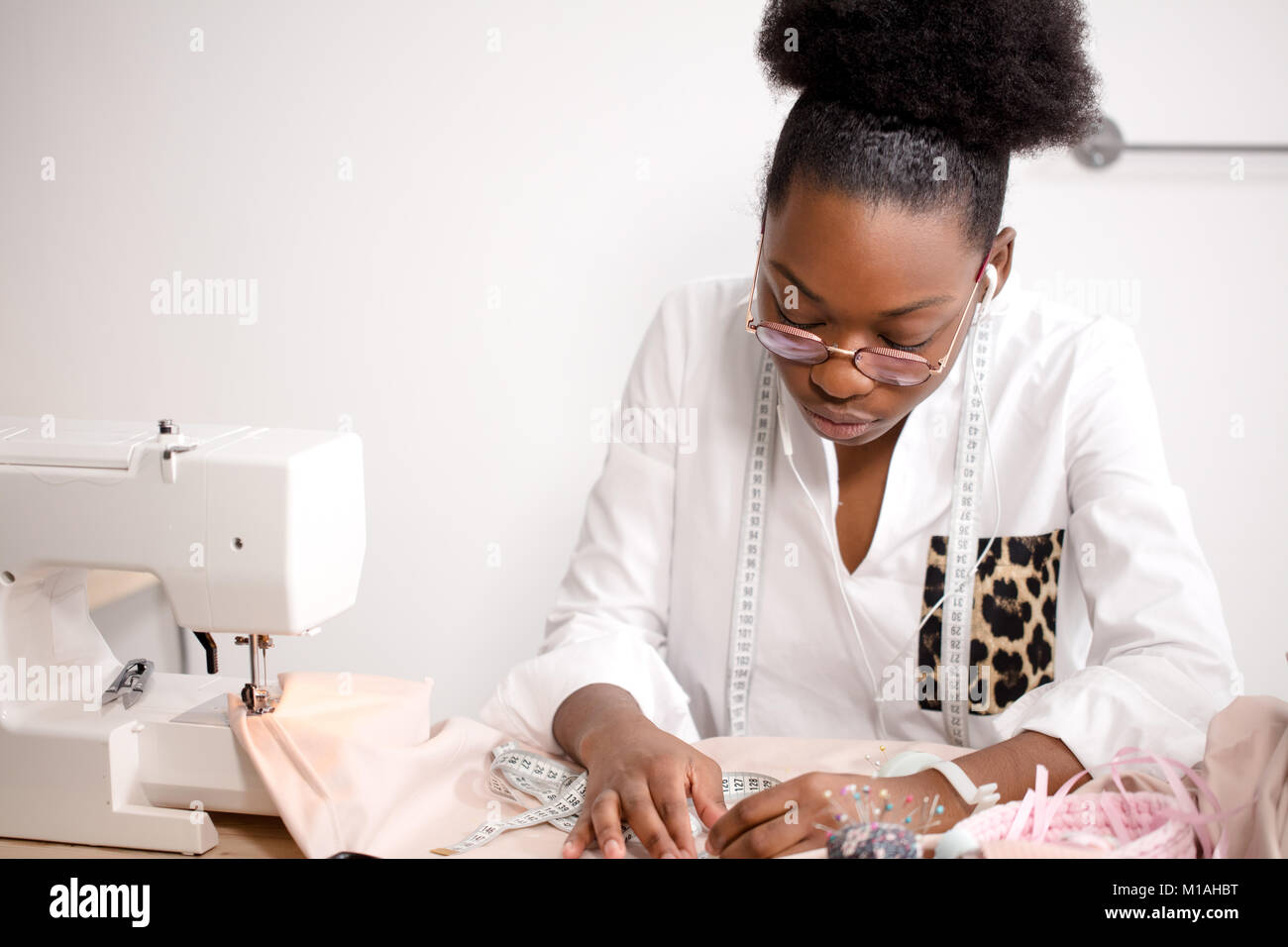 african seamstress working with fabric takes measures - Stock Image
