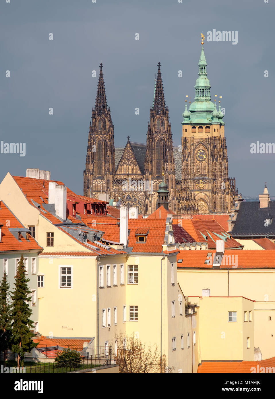 St. Vitus cathedral and roofs of Old Prague with dramatic sky. - Stock Image