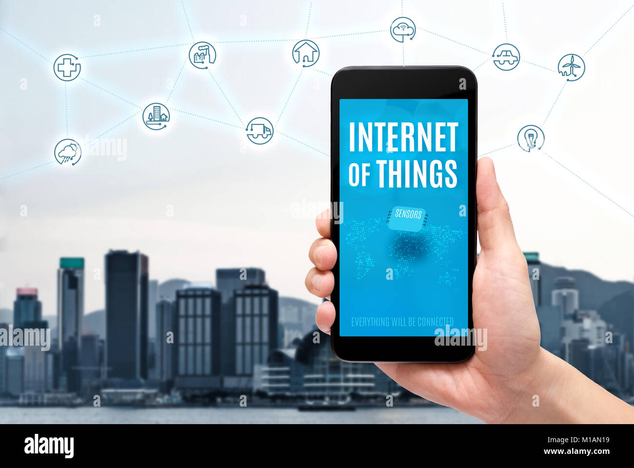 Hand holding mobile with Internet of things (iot) word on screen with icon feature glowing in air with blur city - Stock Image