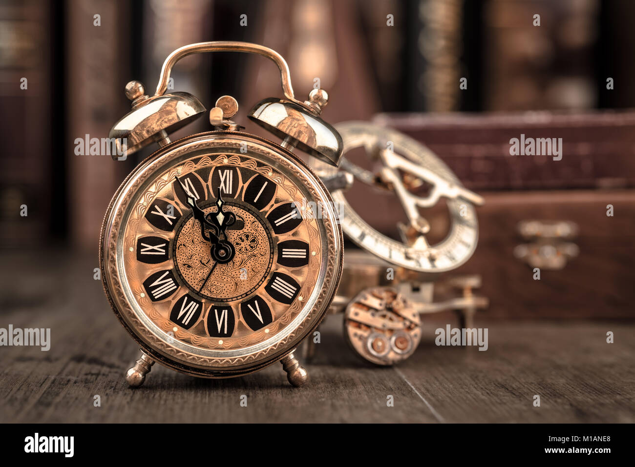 Vintage alarm clock showing five to twelve on the wooden table in study room. Happy New Year 2015! Stock Photo