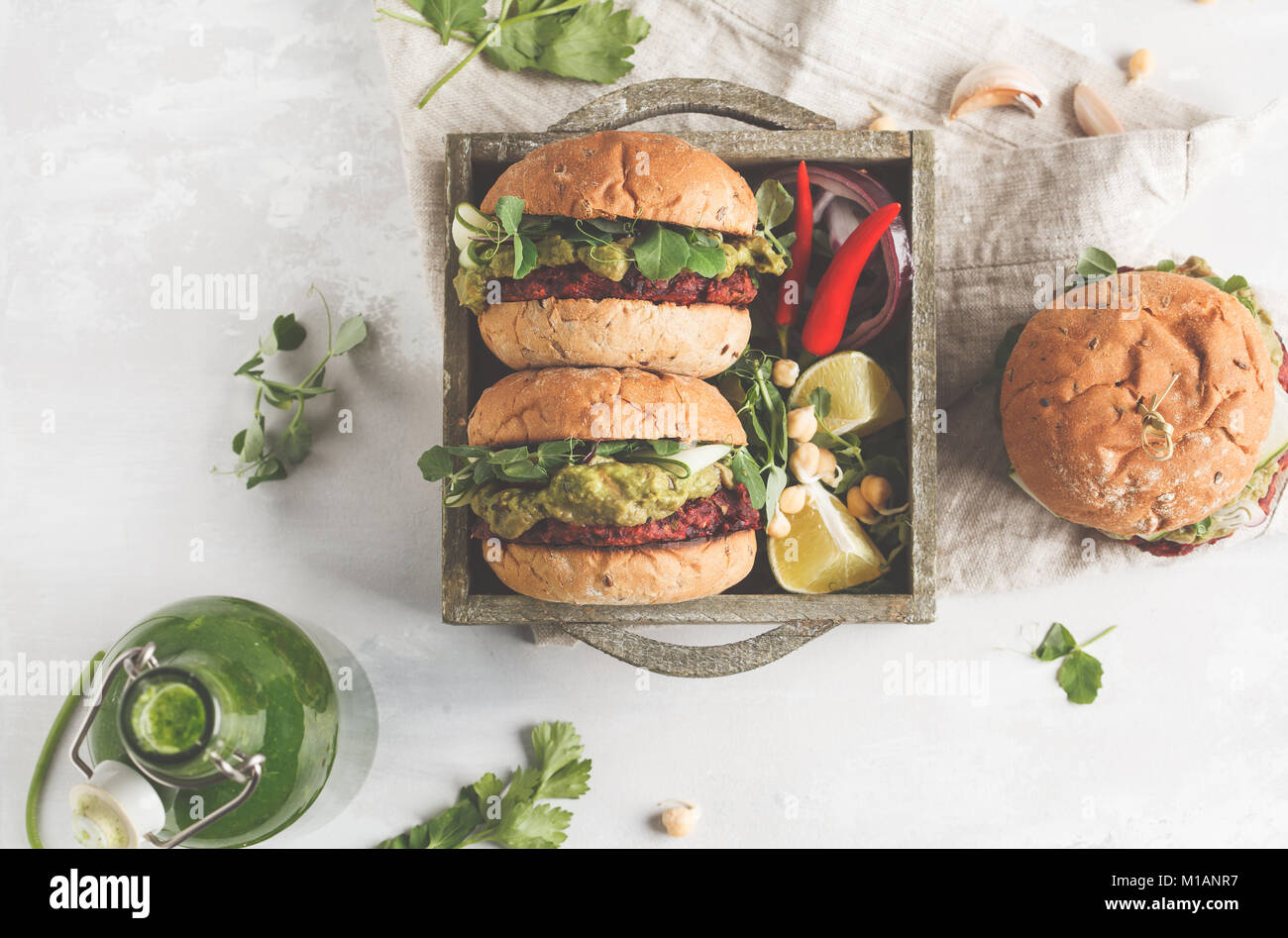 Vegan beet chickpea burgers with vegetables, guacamole and rye buns in wooden box. Healthy vegan food concept. - Stock Image