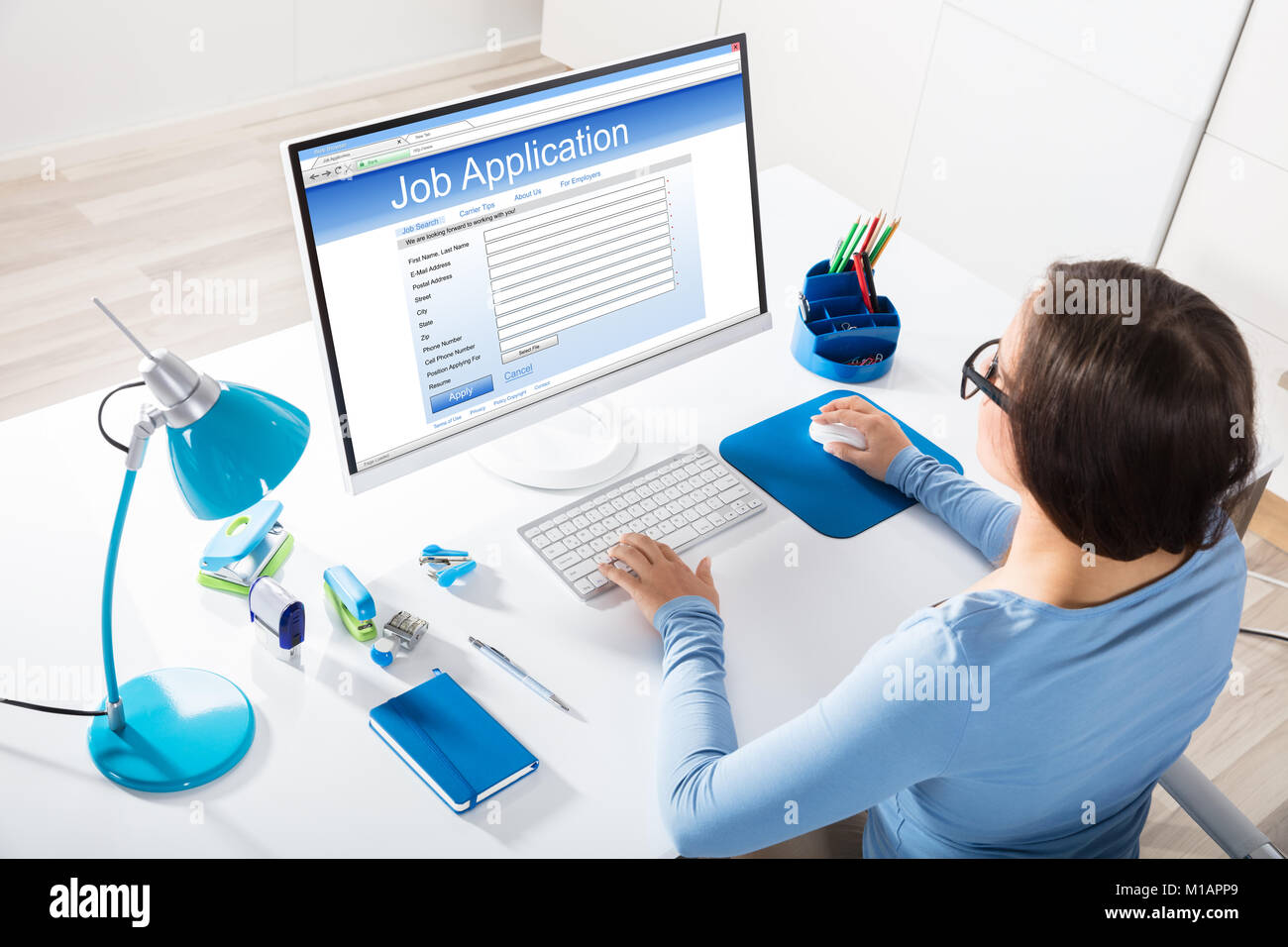 Elevated View Of A Businesswoman Feeling Job Application On Computer In Office - Stock Image