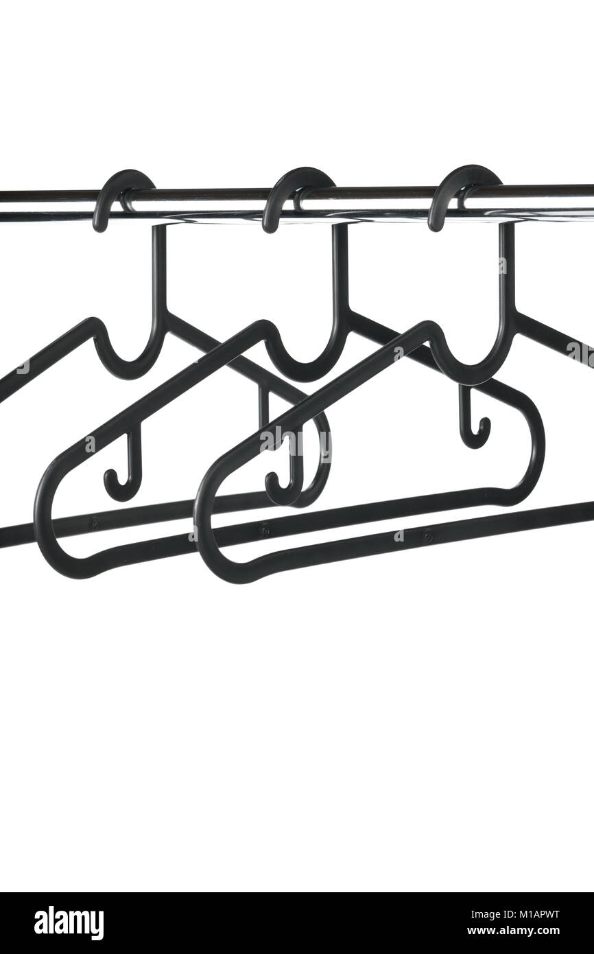 Three empty coat / clothes hangers on a clothes rail with a white background. Potential copy space above and below - Stock Image