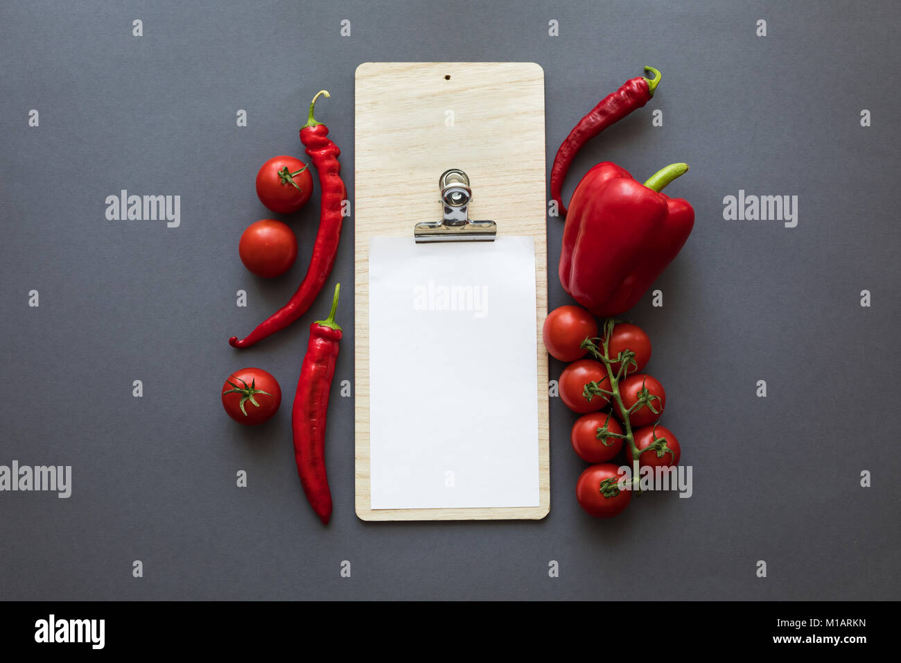 top view of fresh ripe red peppers and tomatoes with blank paper sheet on grey - Stock Image