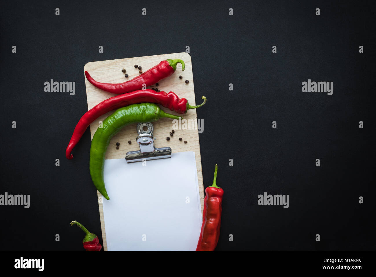 top view of chilli peppers with seeds and blank clipboard isolated on black - Stock Image