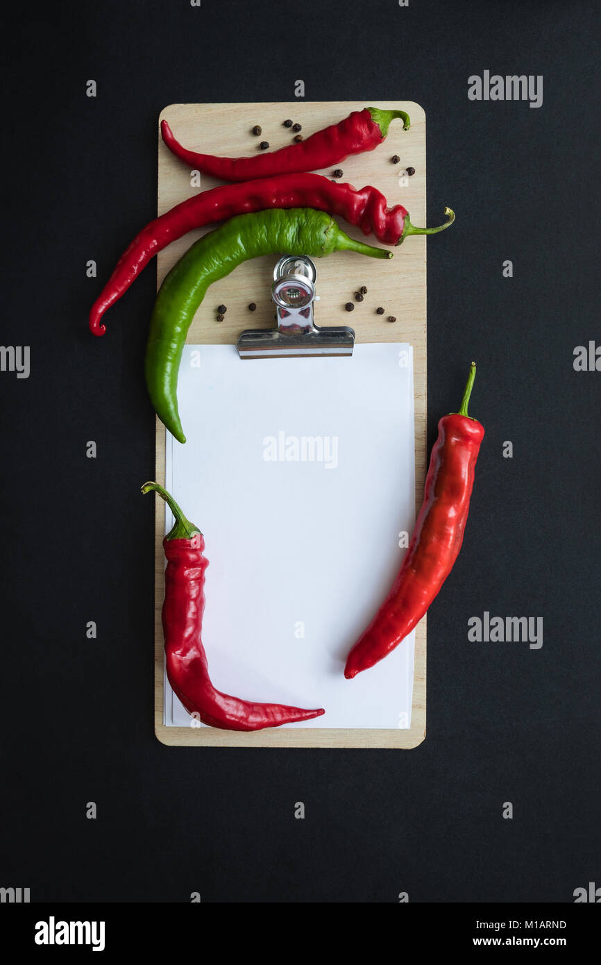 top view of chilli peppers with seeds and blank paper sheet on clipboard isolated on black - Stock Image