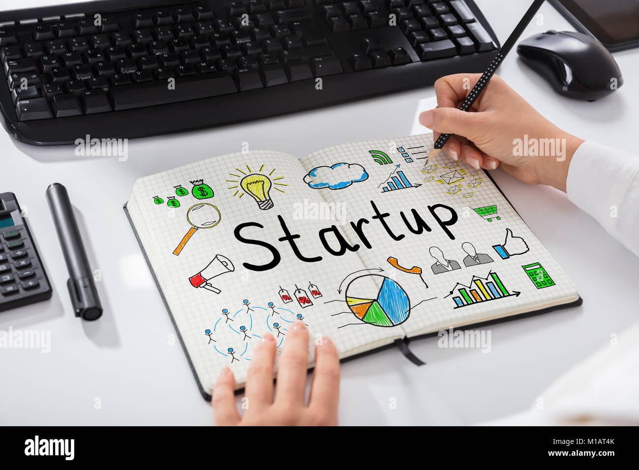 Close-up Of A Businesswoman Drawing Start Up Chart On Notebook Over Desk - Stock Photo