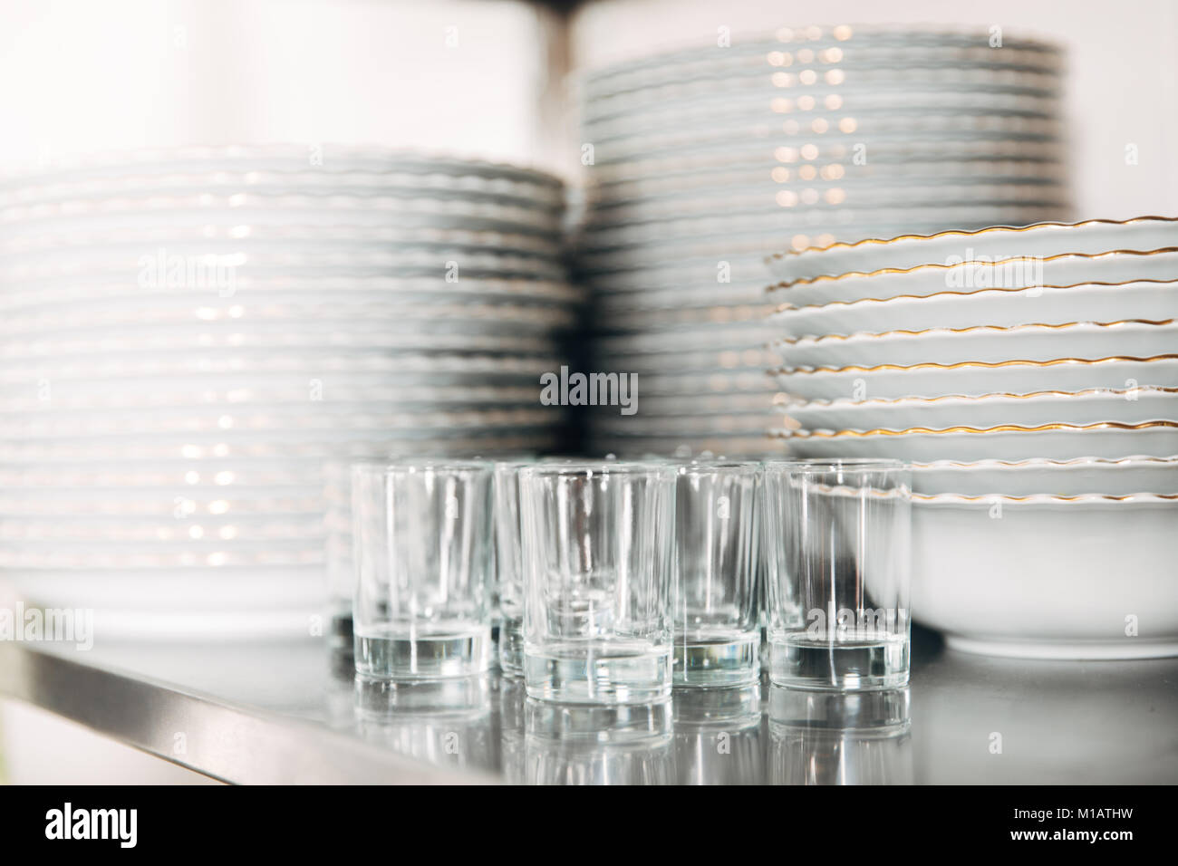 close-up shot of stacked clean tableware and glasses at restaurant Stock Photo