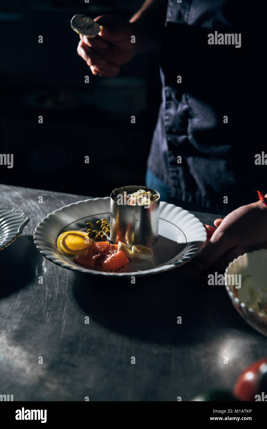 cropped shot of chef preparing salad with metal forming tube at restaurant - Stock Image