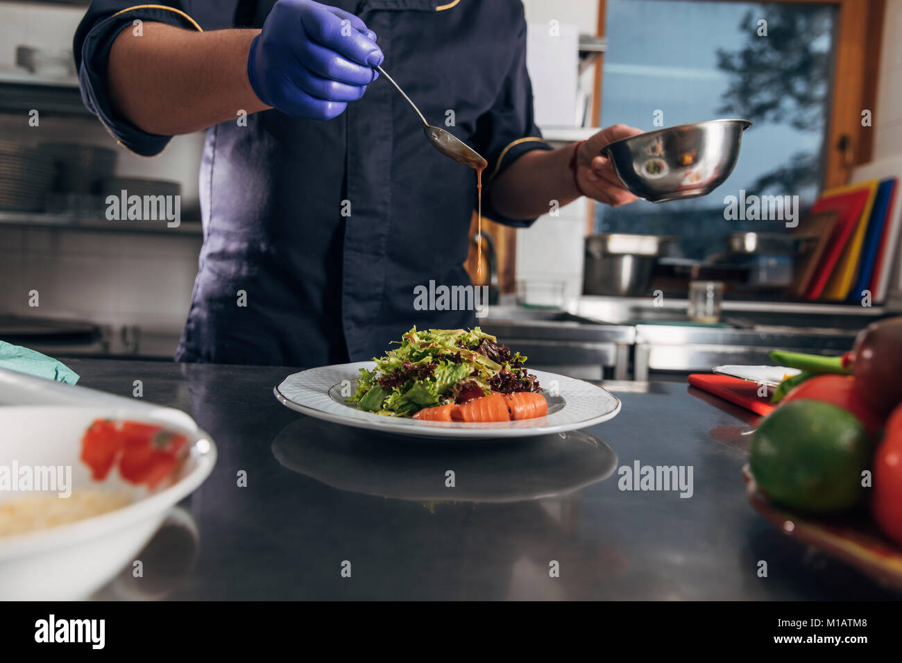 cropped shot of chef pouring sauce onto salad - Stock Image