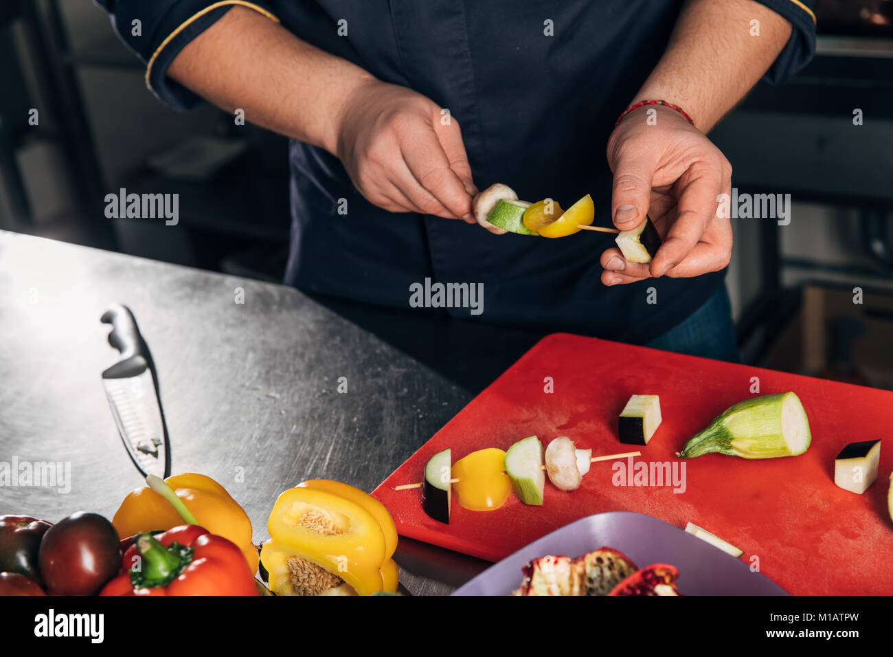 cropped shot of chef piercing vegetables on sticks for grill - Stock Image