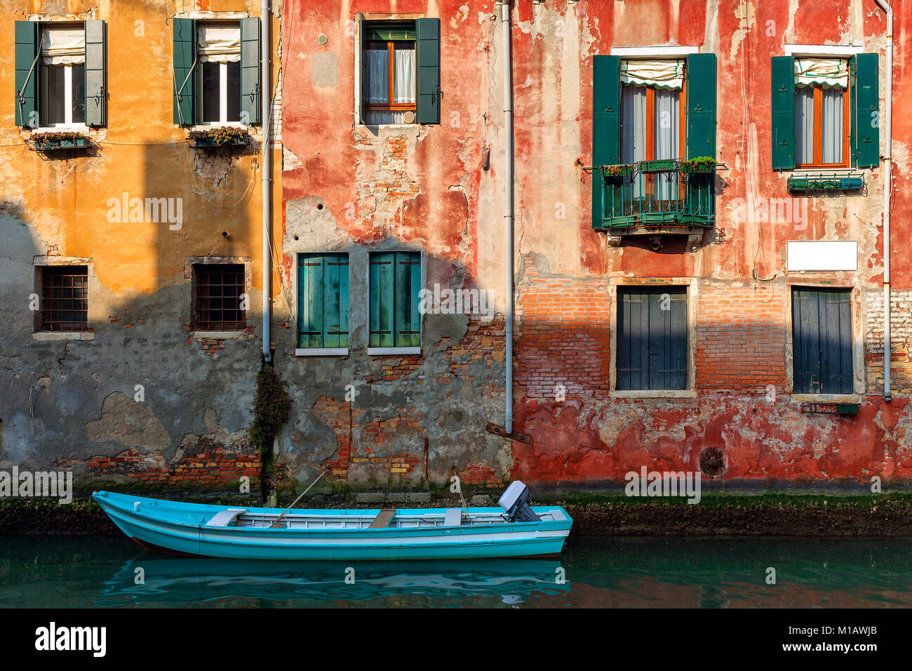 Boat on small canal moored against old colorful brick house in Venice, Italy. - Stock Image