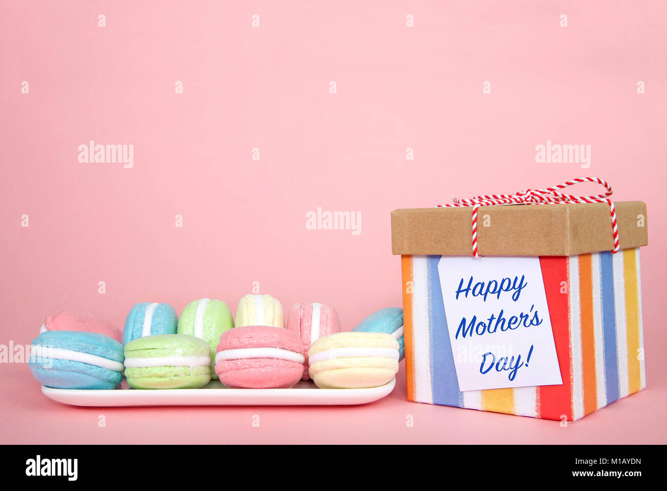 White rectangular plate with pastel colored macaron cookies laying on a pink background, colorful striped present - Stock Image