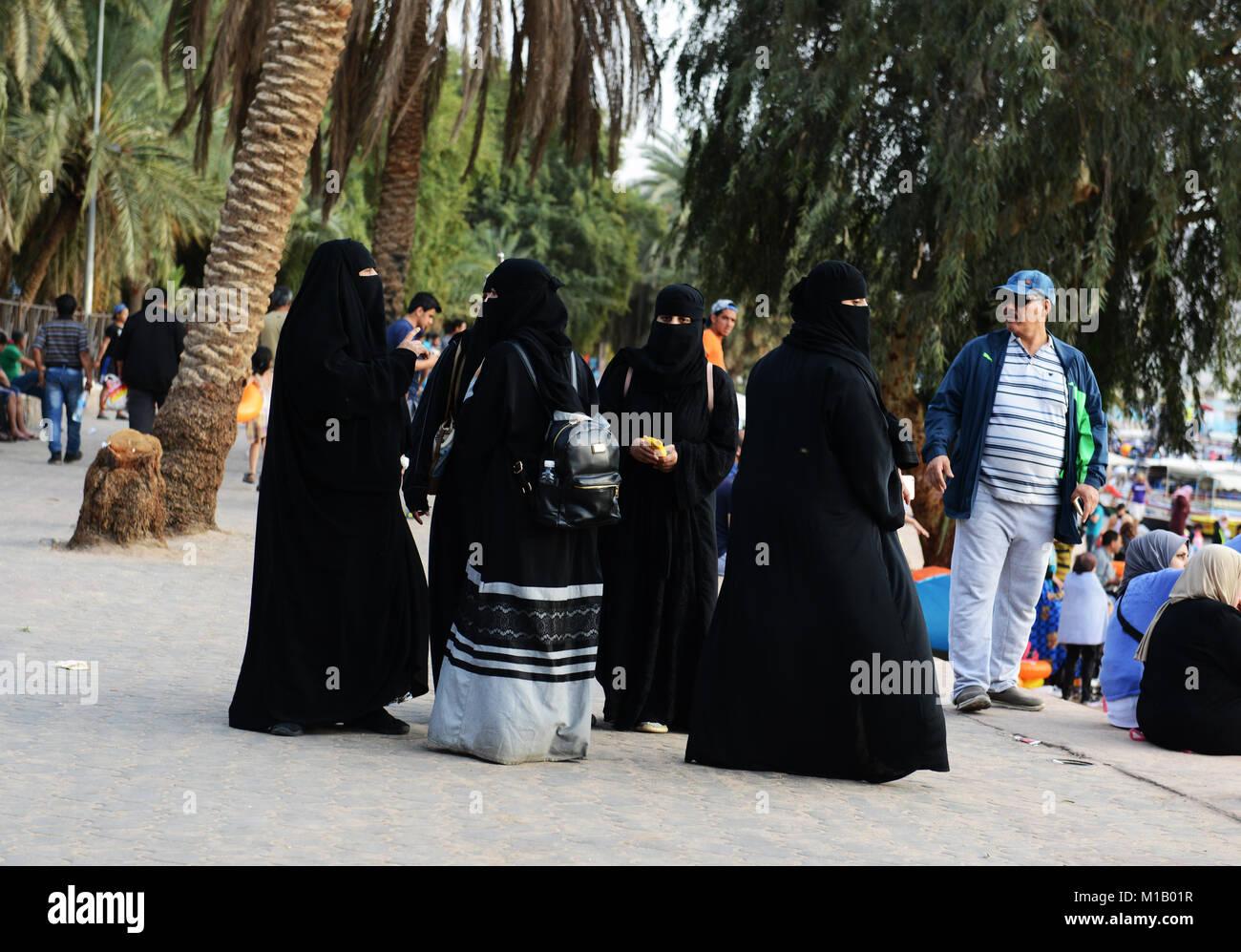 Veiled women on Al-Ghandour Beach in Aqaba, Jordan. - Stock Image