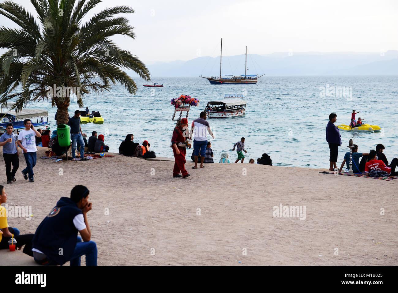 A traditional Tamarind juice vendor walking on Al-Ghandour Beach in Aqaba, Jordan. - Stock Image
