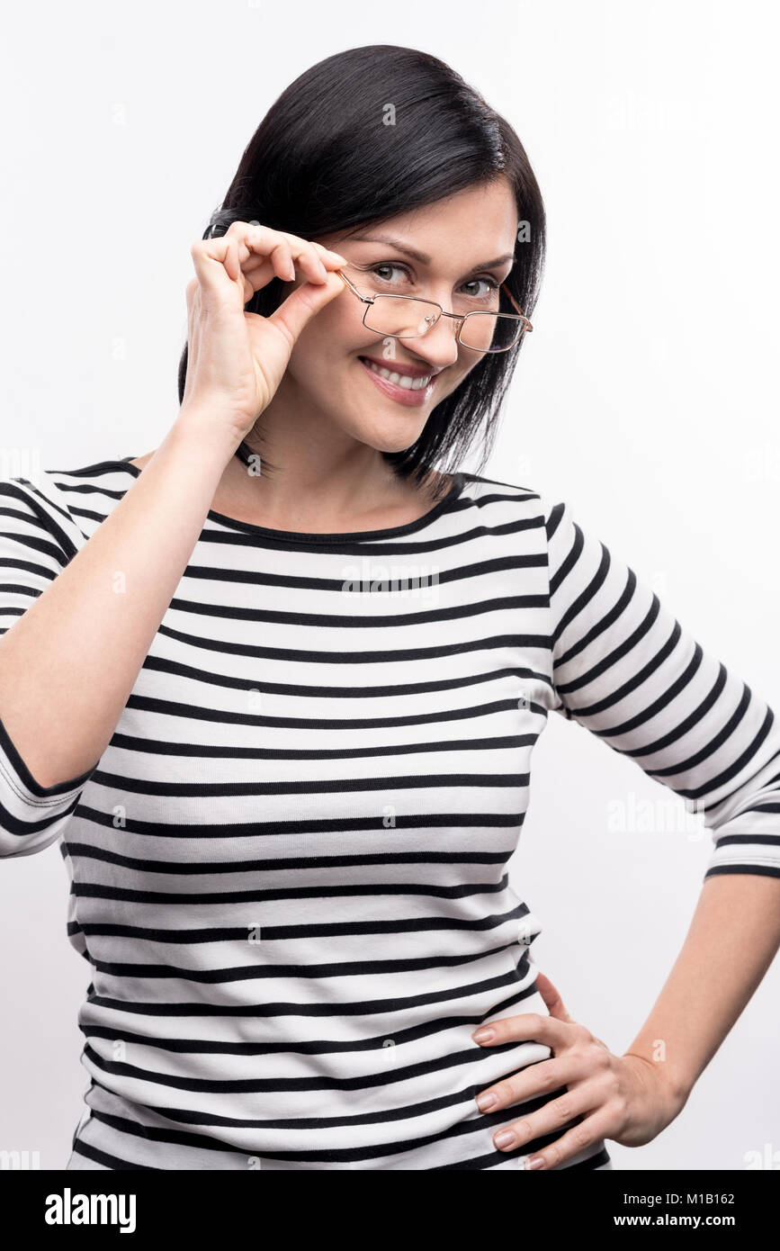 Beautiful woman posing while touching her eyeglasses rim - Stock Image