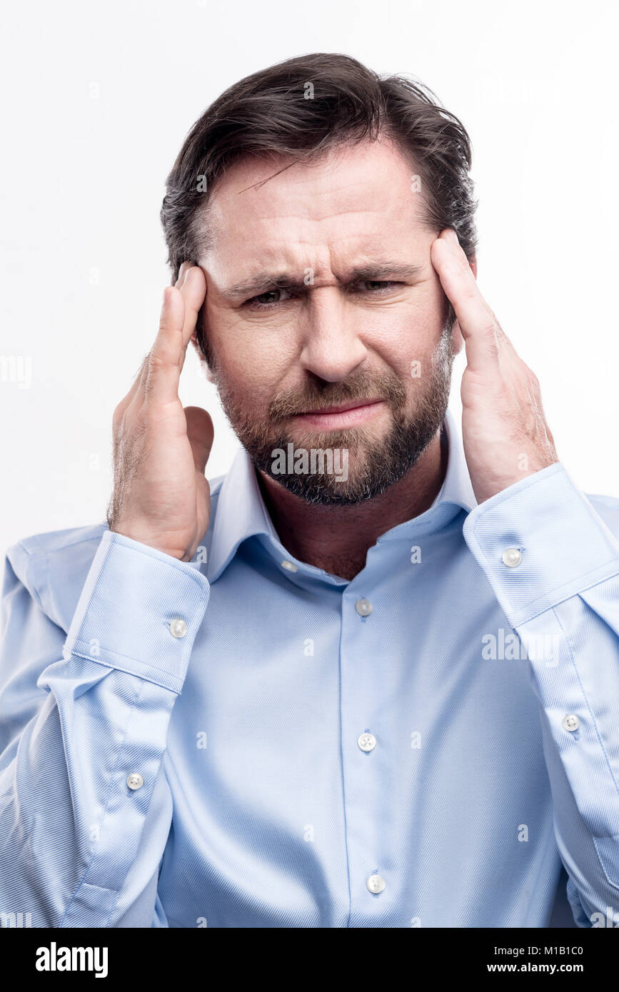Bearded middle-aged man suffering from migraine Stock Photo