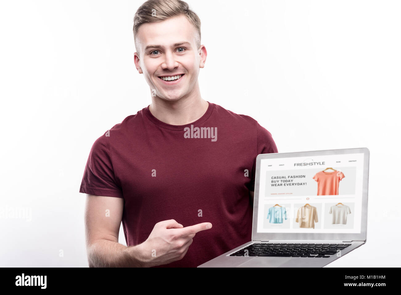 Charming man showing website of online clothes shop - Stock Image