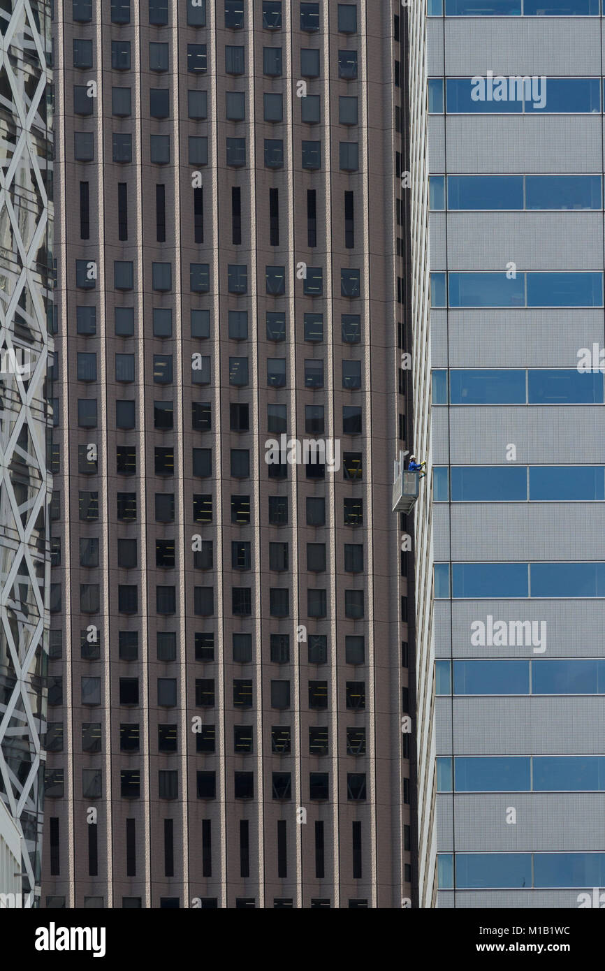 Window cleaners on Shinjuku L Tower with Tokyo skyscrapers behind. Tokyo, Japan. Friday January 19th 2018 - Stock Image