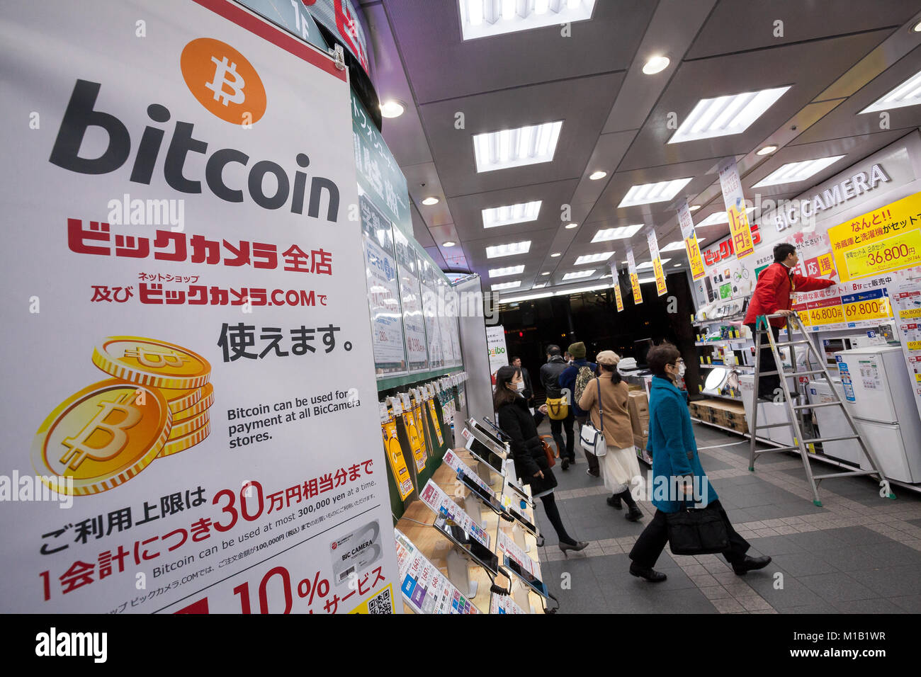 Signs advertising the ability to pay with Bitcoins in Bic Camera, Yurakucho, Tokyo, Japan. Friday January 19th 2018. - Stock Image