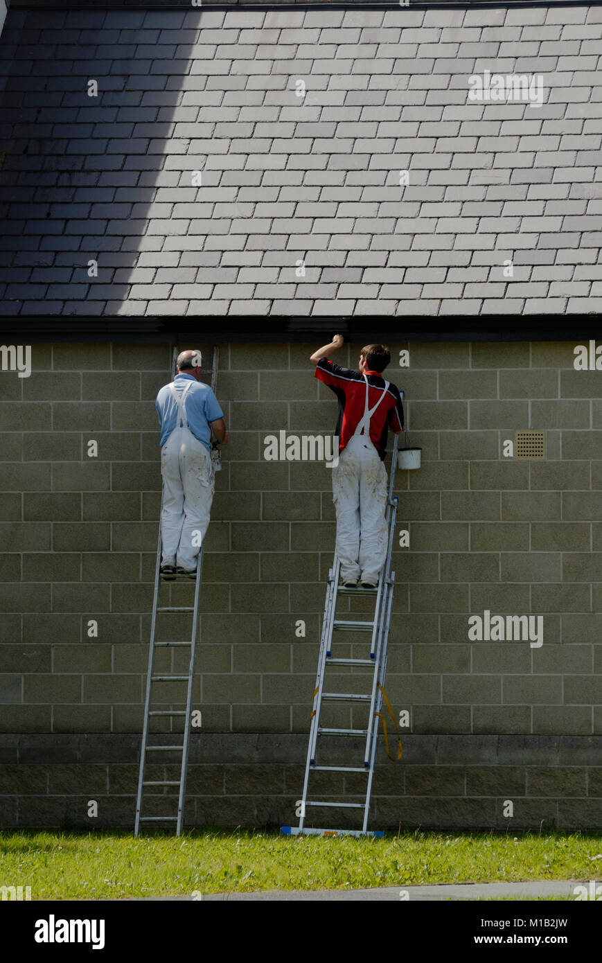 Workmen painting the guttering of Aberystwyth Police Station, Wales. Stock Photo