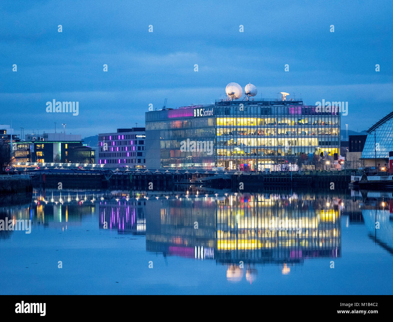 Evening view of BBC Scotland headquarters reflected in River Clyde in Glasgow , Scotland, United Kingdom - Stock Image