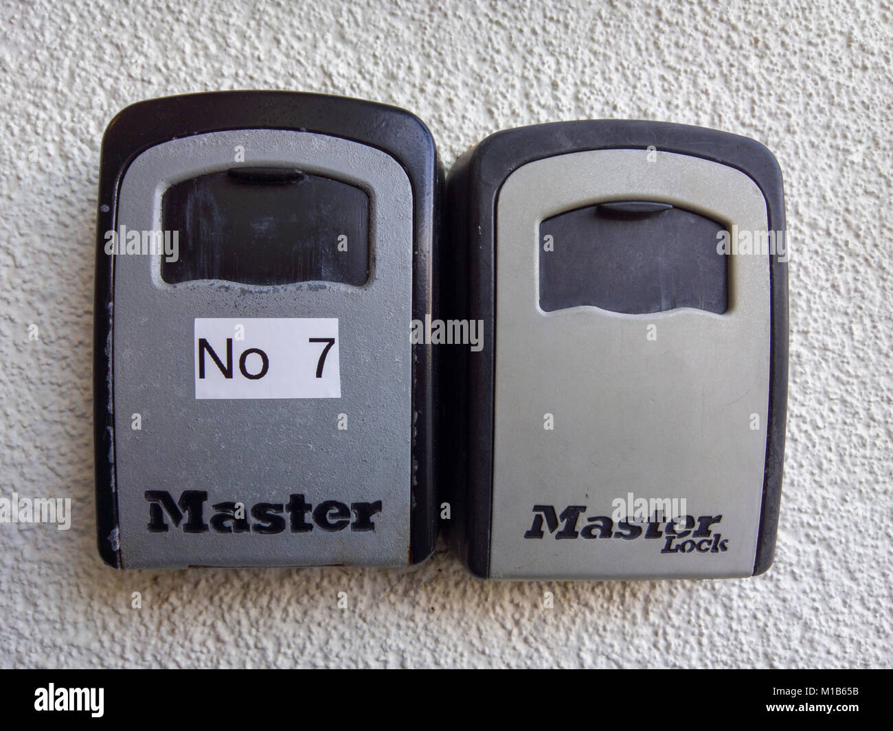 A pair of Master Lock combination key safes outside apartments. - Stock Image