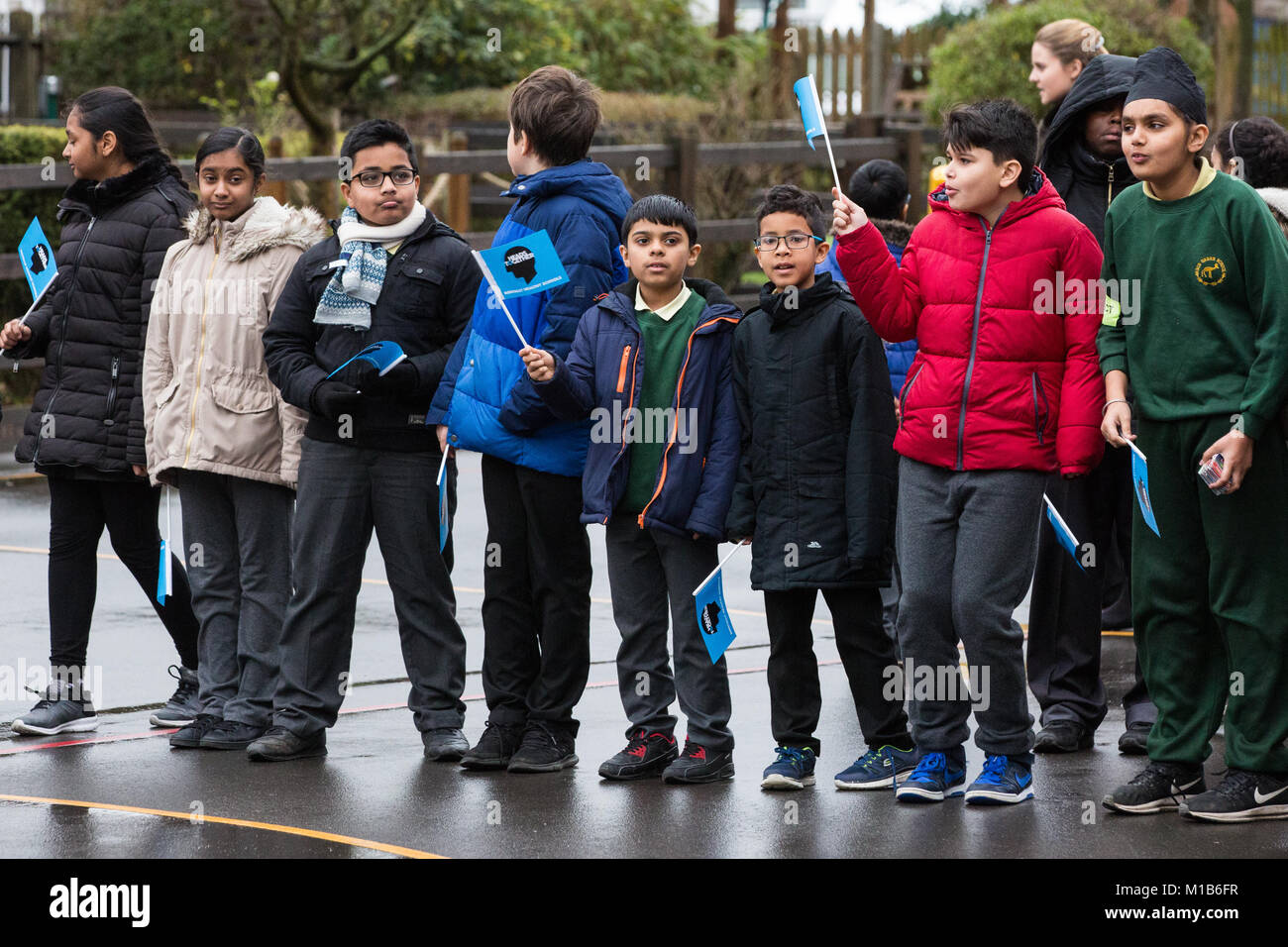 London, UK. 23rd January, 2018. Schoolchildren await the arrival of the Duchess of Cambridge at Roe Green Junior - Stock Image