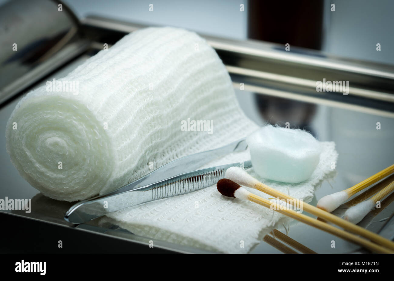 Wound care dressing set on stainless steel plate. Cotton ball with alcohol, cotton stick with povidone-iodine, forceps - Stock Image