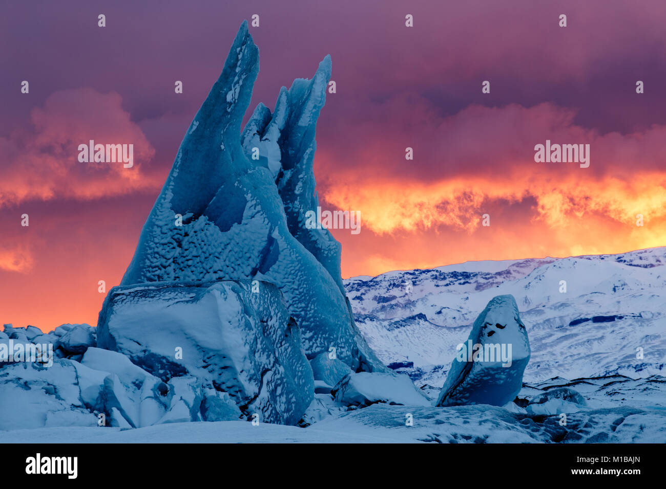A pointy blue iceberg at sunset at Jokulsarlon Lagoon in South Iceland - Stock Image