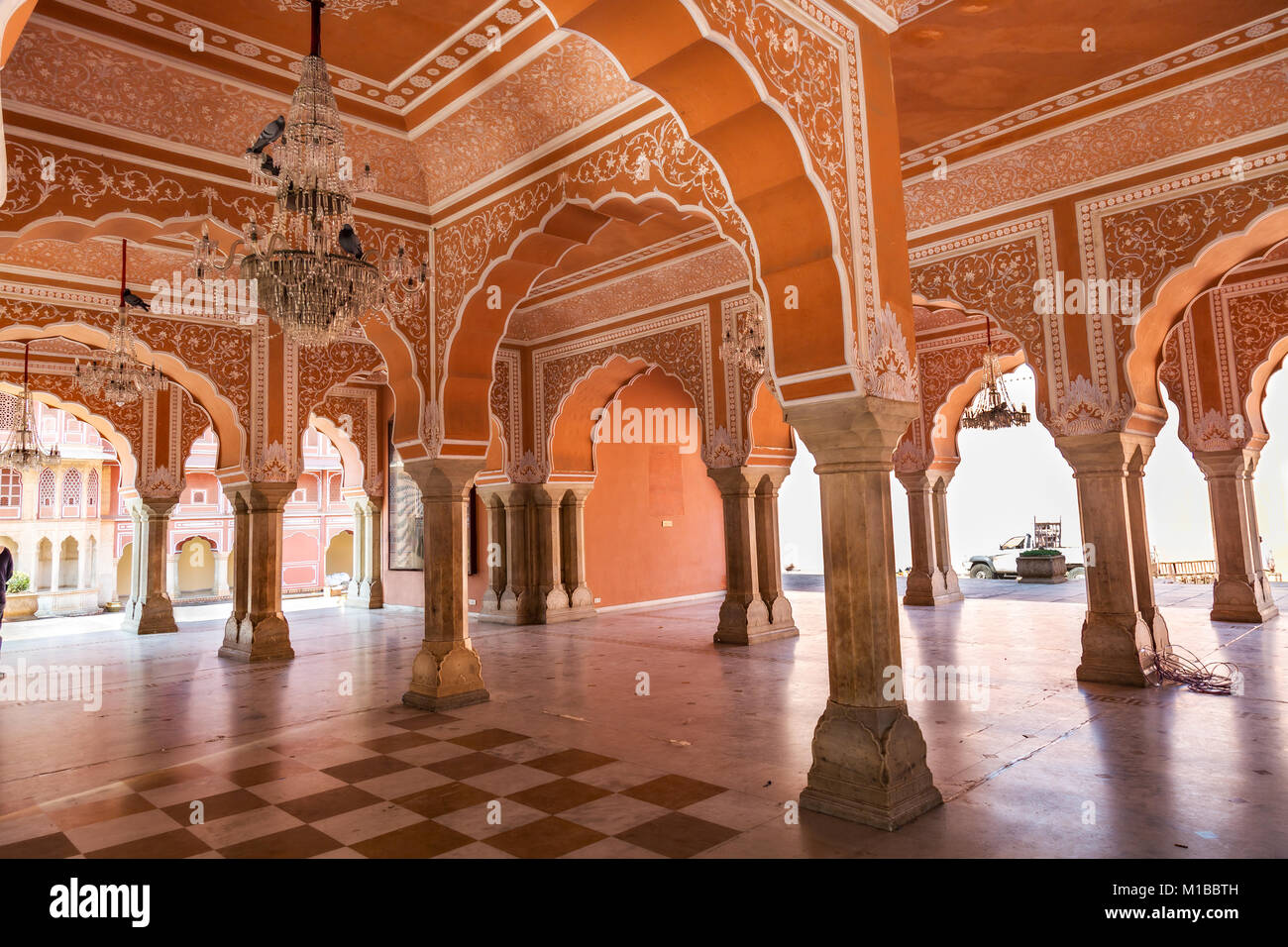 Chandra Mahal at City Palace Jaipur Rajasthan hallway with intricate wall art and pillar structure. - Stock Image