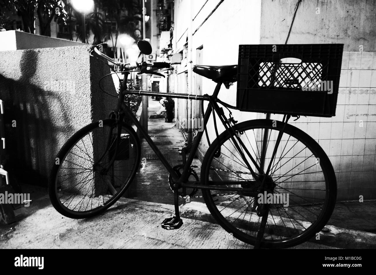 A typical Hong Kong style bike parked outside an apartment building - Stock Image