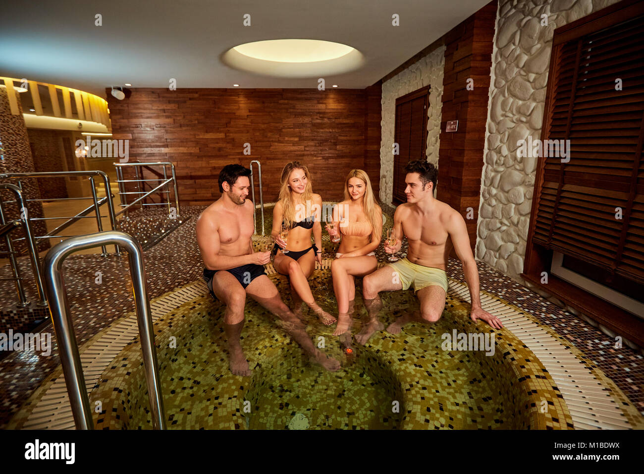 Friends in swimsuits laugh at the jacuzzi in the spa center. - Stock Image