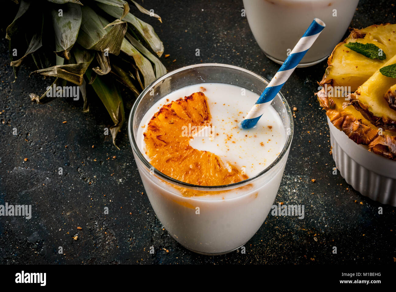 Indian food and drink, Caramelized Pineapple Lassi cocktail, dark blue background copy space - Stock Image