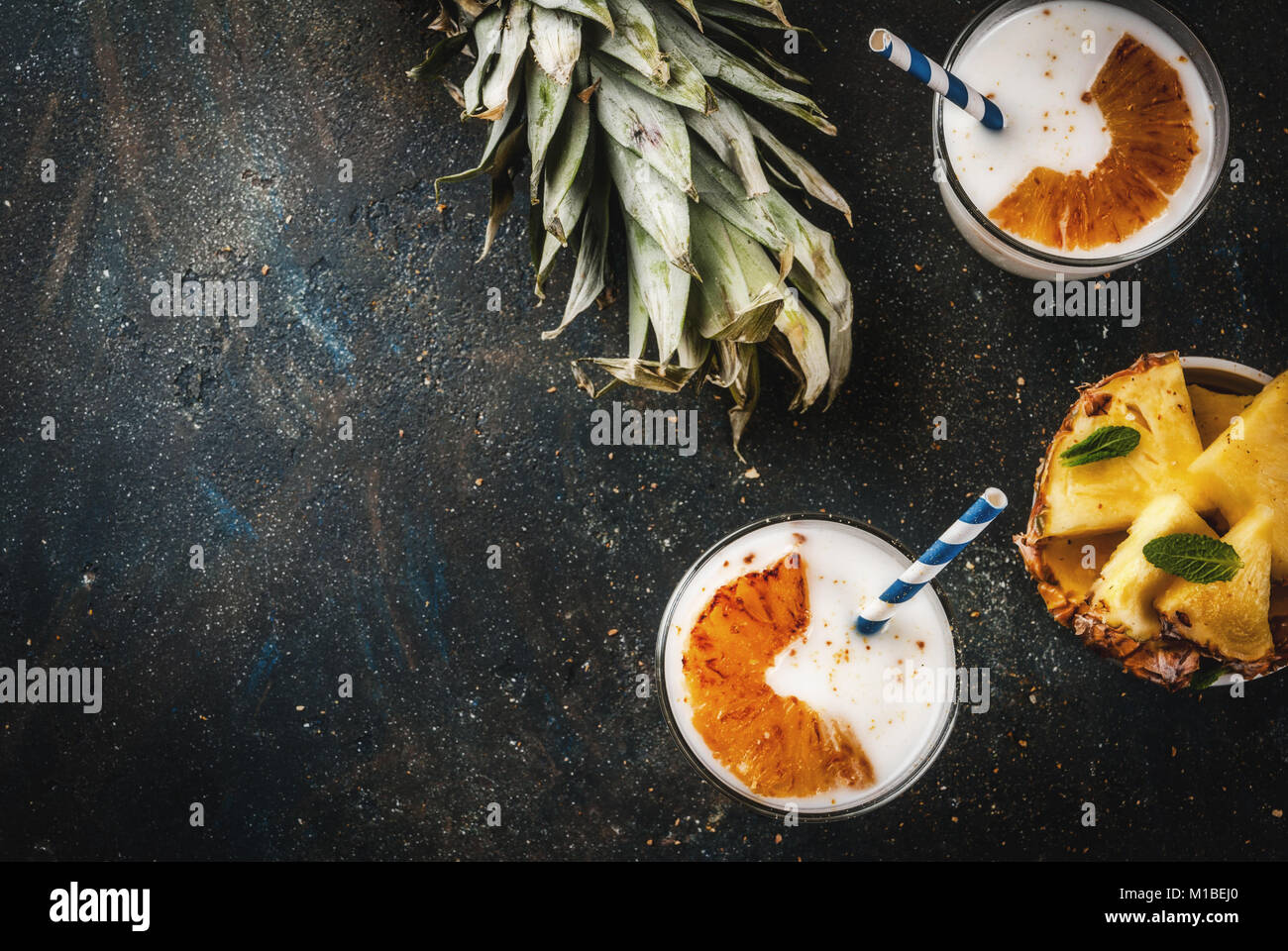 Indian food and drink, Caramelized Pineapple Lassi cocktail, dark blue background copy space top view - Stock Image