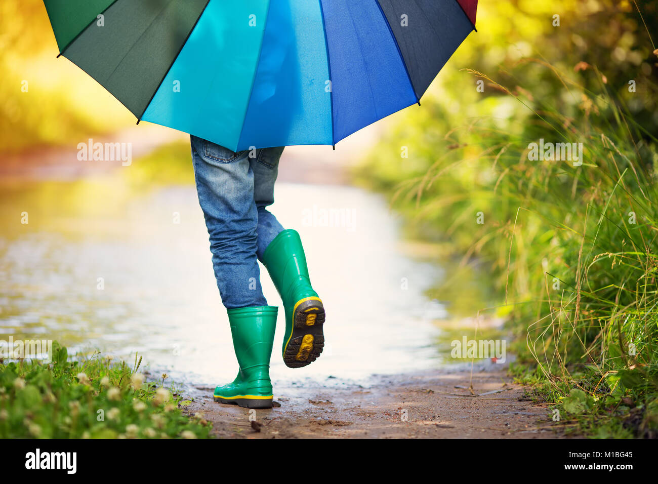 Child walking in wellies in puddle on rainy weather Stock Photo