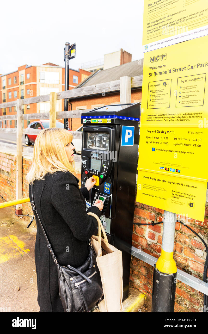 Lady buying car park ticket, woman buying car park ticket, purchasing car park ticket, using car park machine, choosing - Stock Image