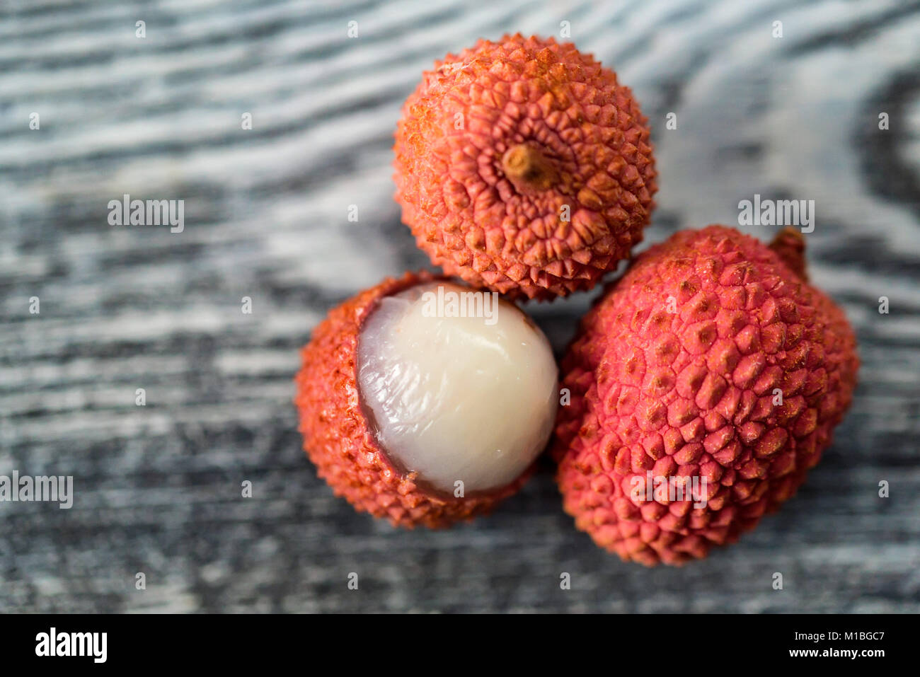 Three lychee fruits on wooden background close - Stock Image