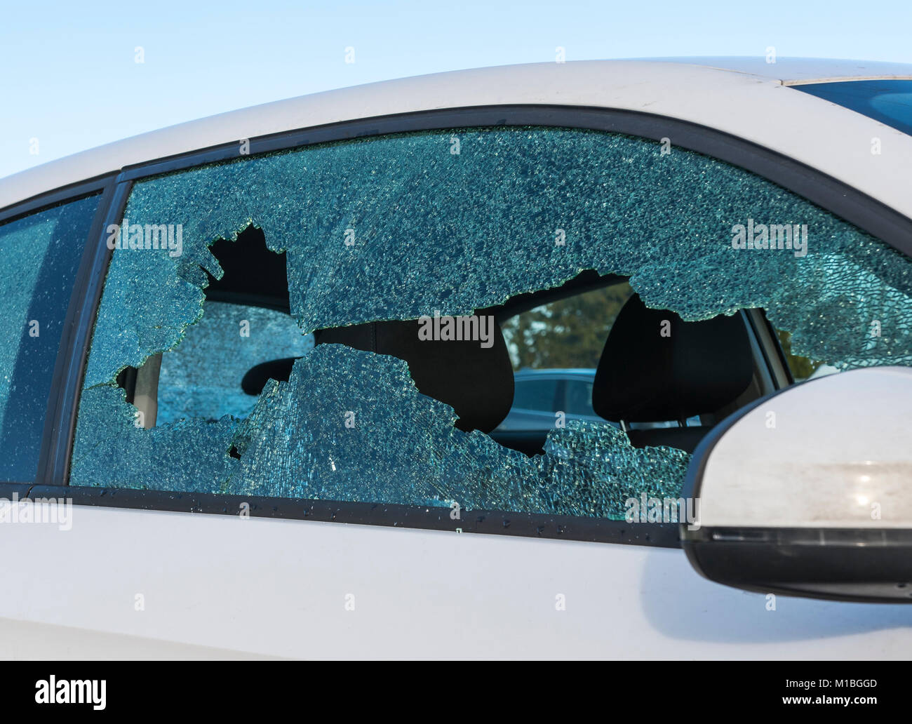 Vandalised car with a smashed broken window. - Stock Image