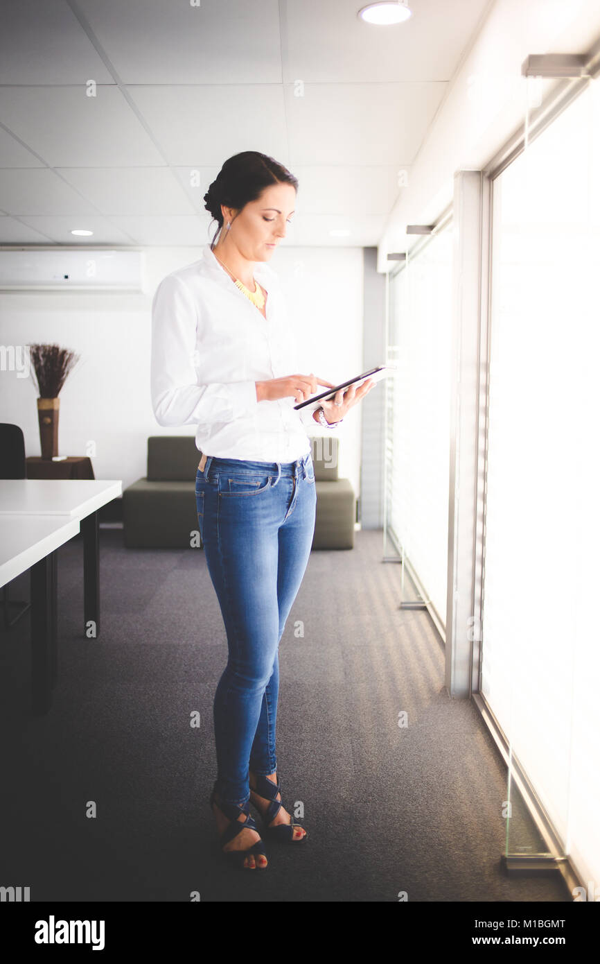 Beautiful brunette business woman standing in a boardroom working on a tablet computer - Stock Image
