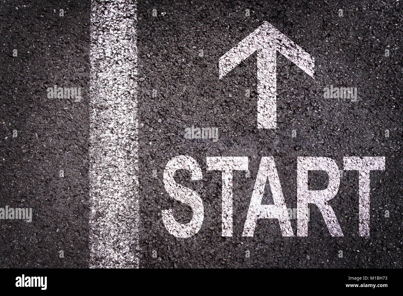 Word Start and an arrow written on an asphalt road background - Stock Image
