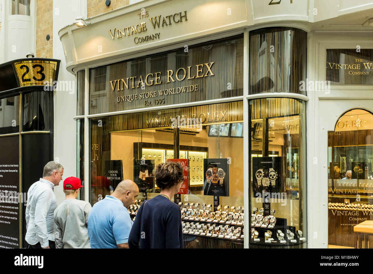 Peple looking at vintage watches through shop window of The Vintage Watch Company, Burlington Arcade, London, UK - Stock Image