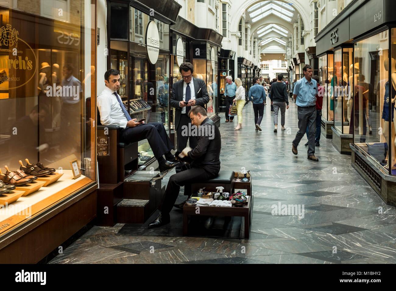 Shoeshine boy (man) cleaning customers shoes at Burlington Arcade, London, UK - Stock Image