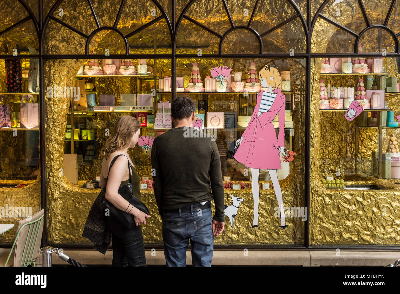 Young couple looking through the window of upmarket bakery Ladurée in Burlington Archade in London, UK - Stock Image